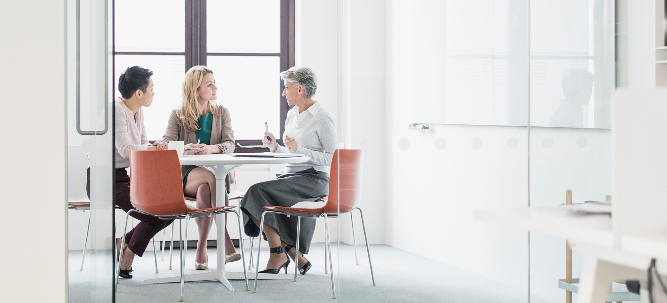 Three women sitting at table in modern office